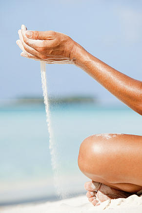 Woman letting sand flow through hands, Maldives